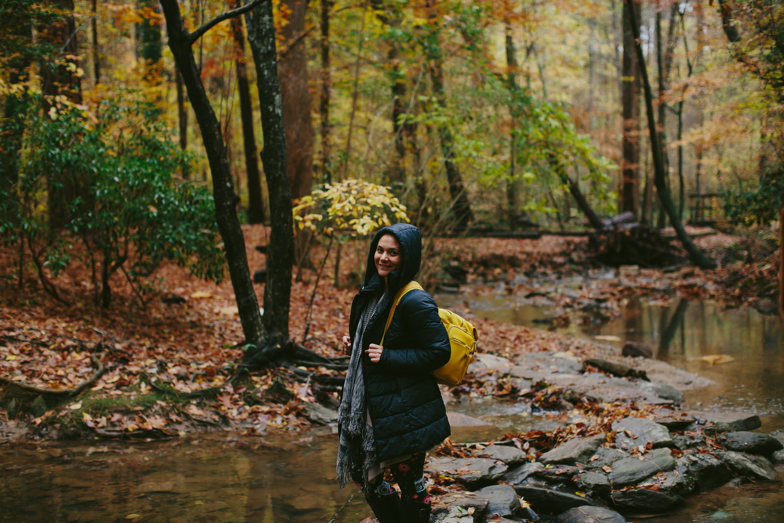 photographer hiking in the woods in fall in north carolina