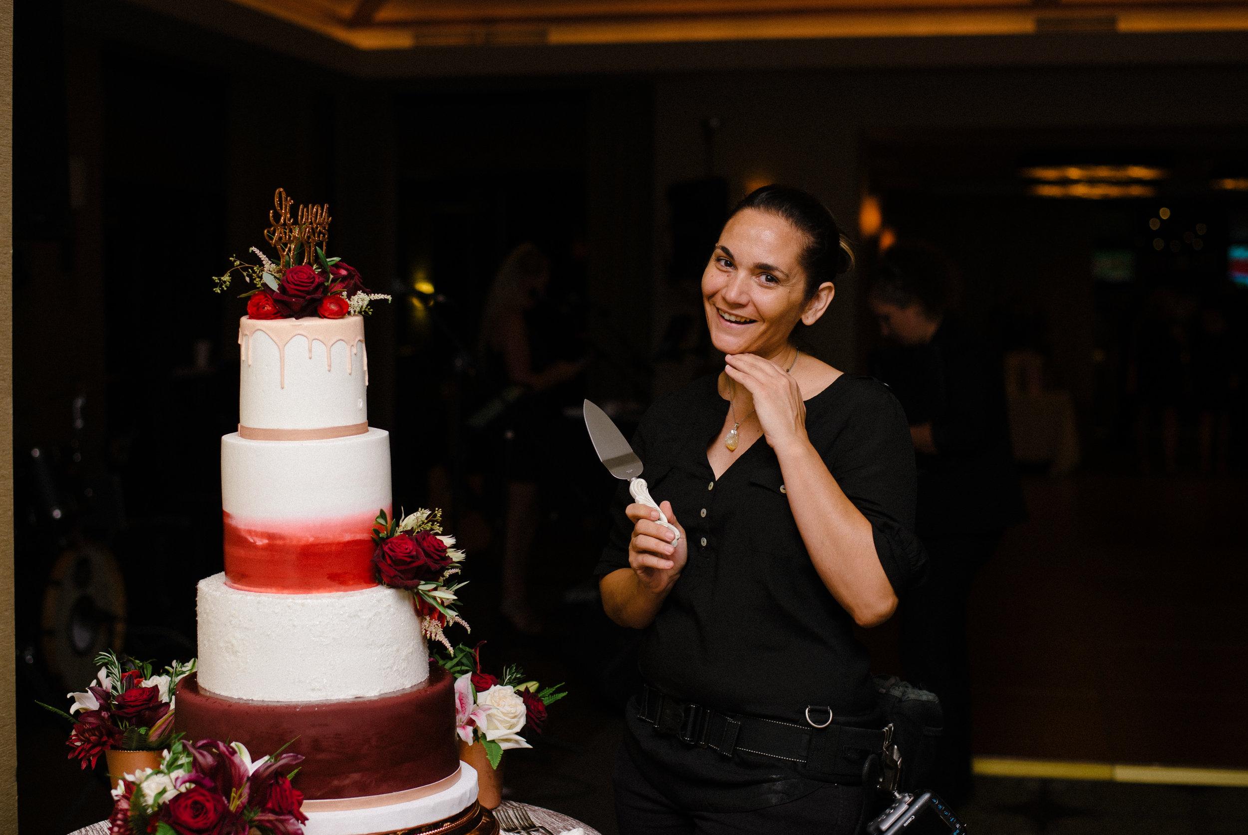 Awkward Wedding Photographer posing next to wedding cake
