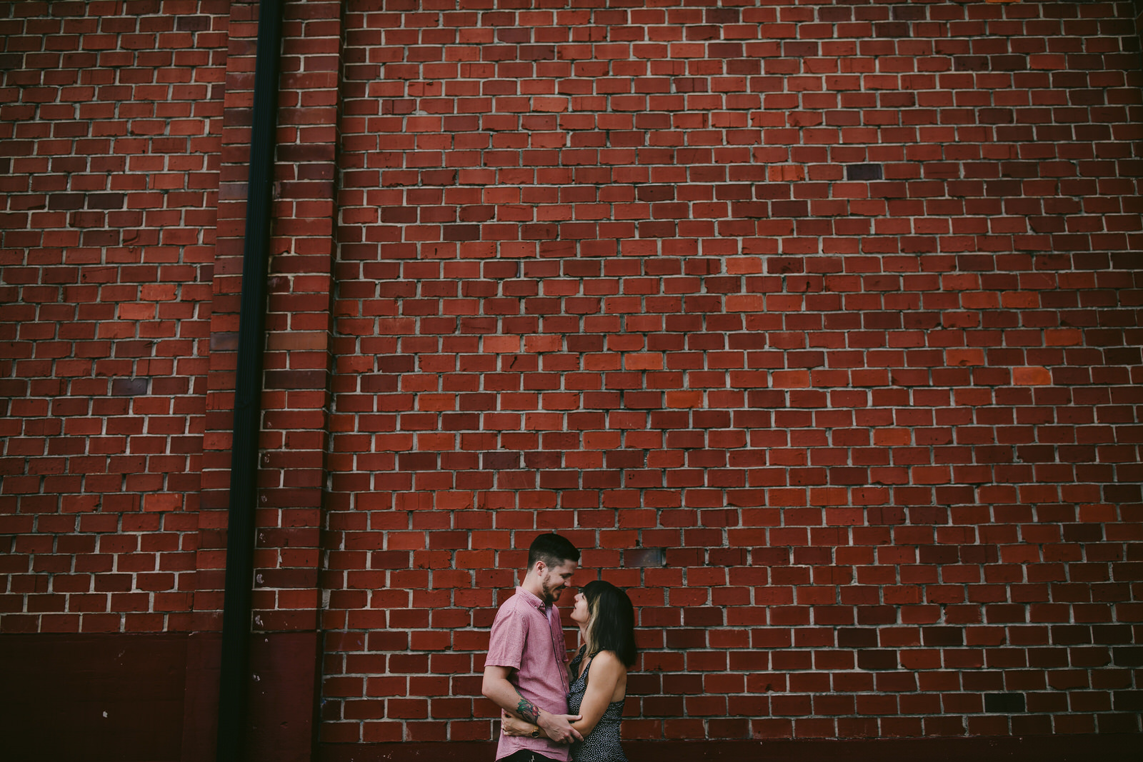 adorable-couples-session-jacksonville-florida-brick-wall-cute-indie-tattooed-couple-embracing-tiny-house-photo.jpg