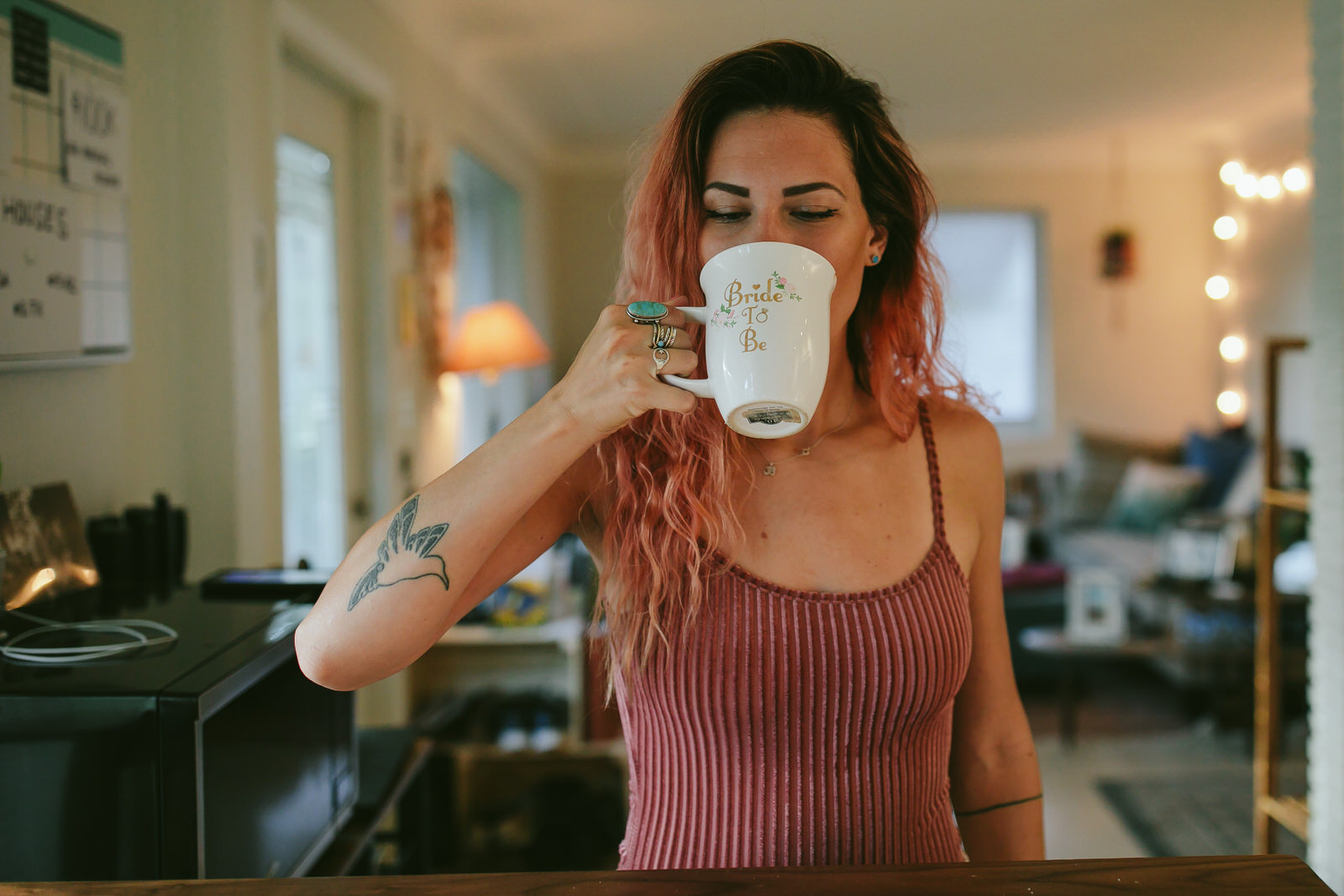 tattooed girl drinking coffee at home