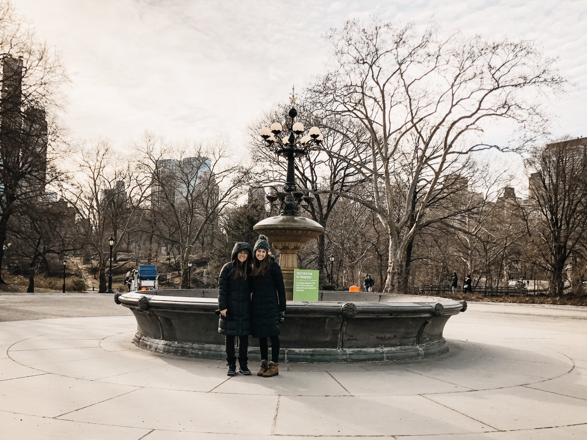 Photo taken by random person passing by of Samantha McHenry and Sara Kreski in front of (not real) Friends Fountain in Central Park.