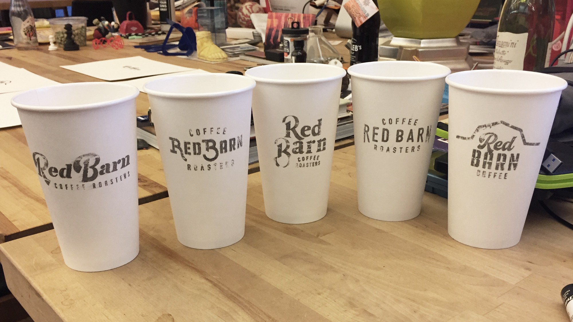 Adam presented his first round of logos on coffee cups.