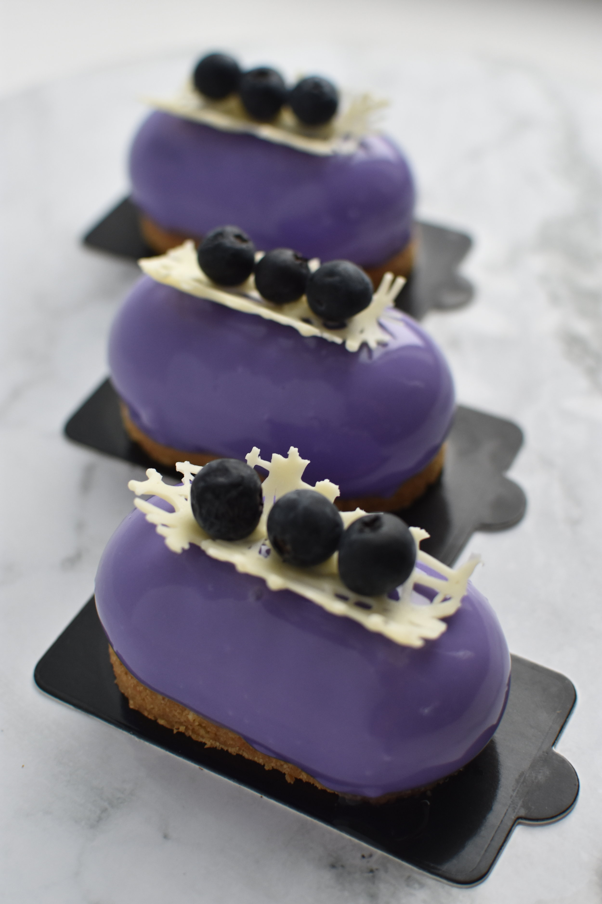 BLUEBERRY BLISS  Biscuit base, blueberry cheesecake, blueberry compote, mirror glaze, blueberries and white chocolate.  $6.90 each  Minimum Order Quantity : 8