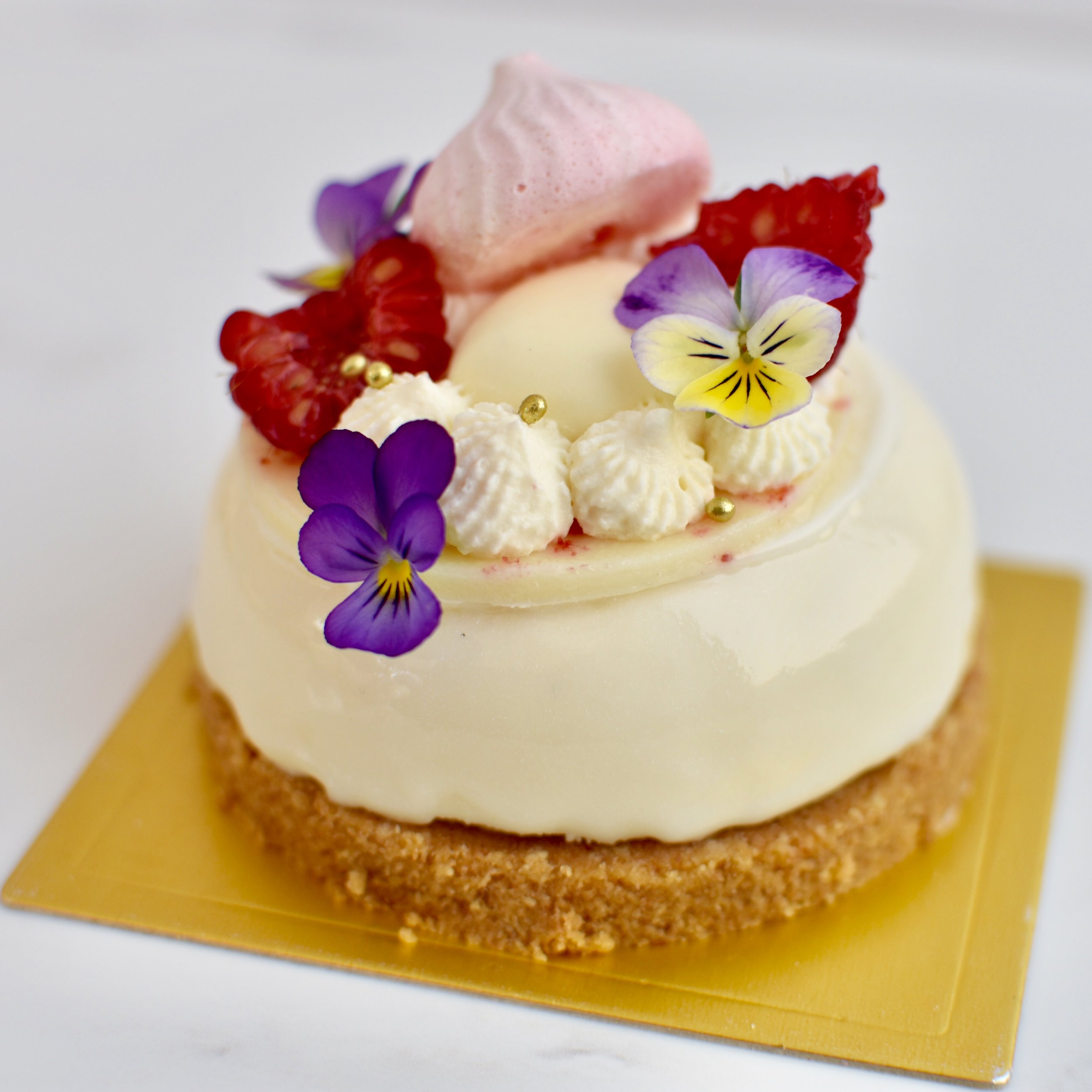 RASPBERRY DREAM  Biscuit base, vanilla cheesecake, raspberry compote, white chocolate glaze, white chocolate disc, raspberries.  $7.50 each  Minimum Order Quantity : 10