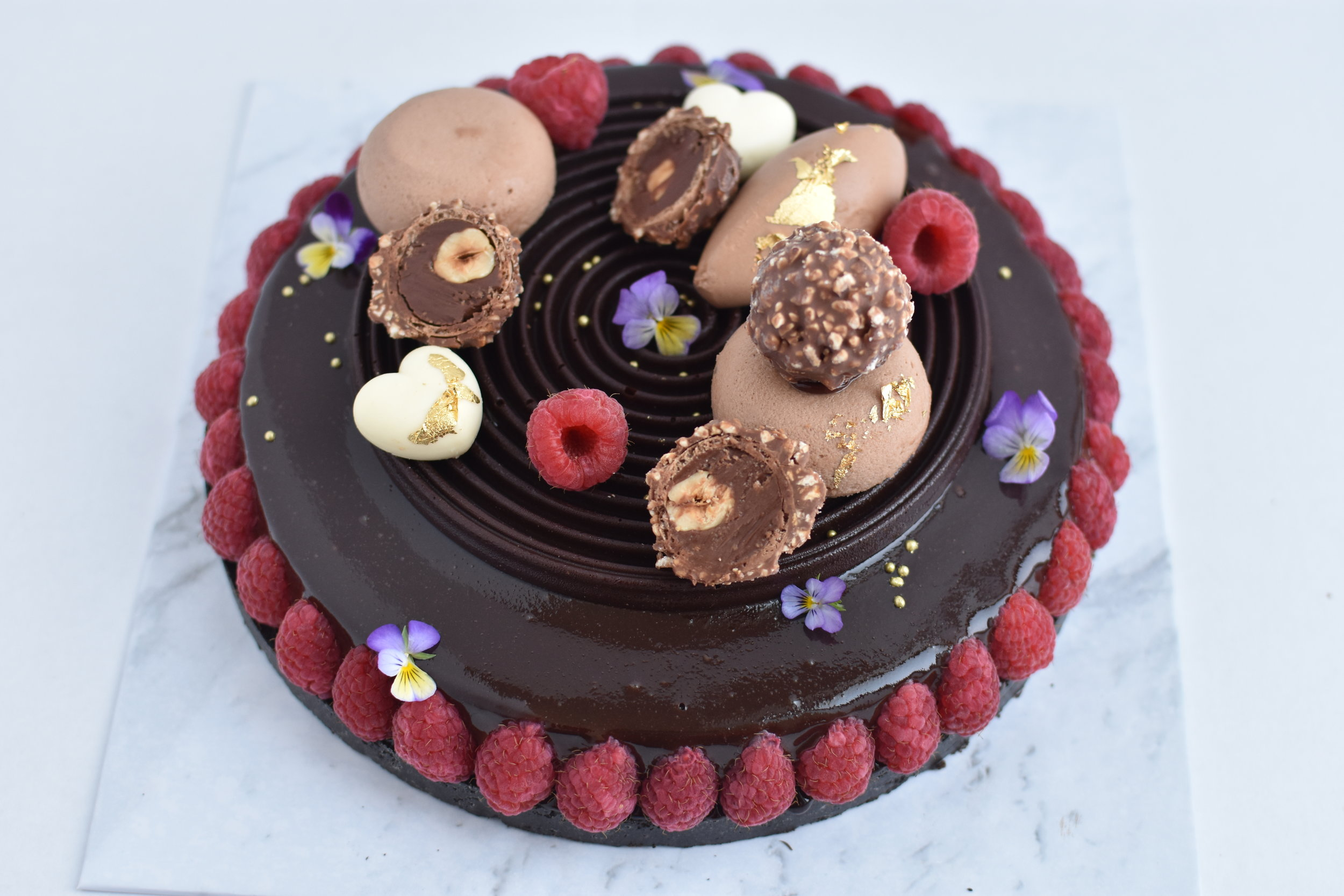 "NUTELLA ENTREMET  Hazelnut Brownie Base, Nutella Cheesecake, Dark Chocolate Mirror Glaze, Bitter Chocolate Disc, Milk and White Chocolate Mousse, Ferrero, Raspberries, Edible Flowers, Gold Pearls and Gold Leaf.  6"" size $49.00 Feed upto 8  8"" size $69.00 Feed upto 12"