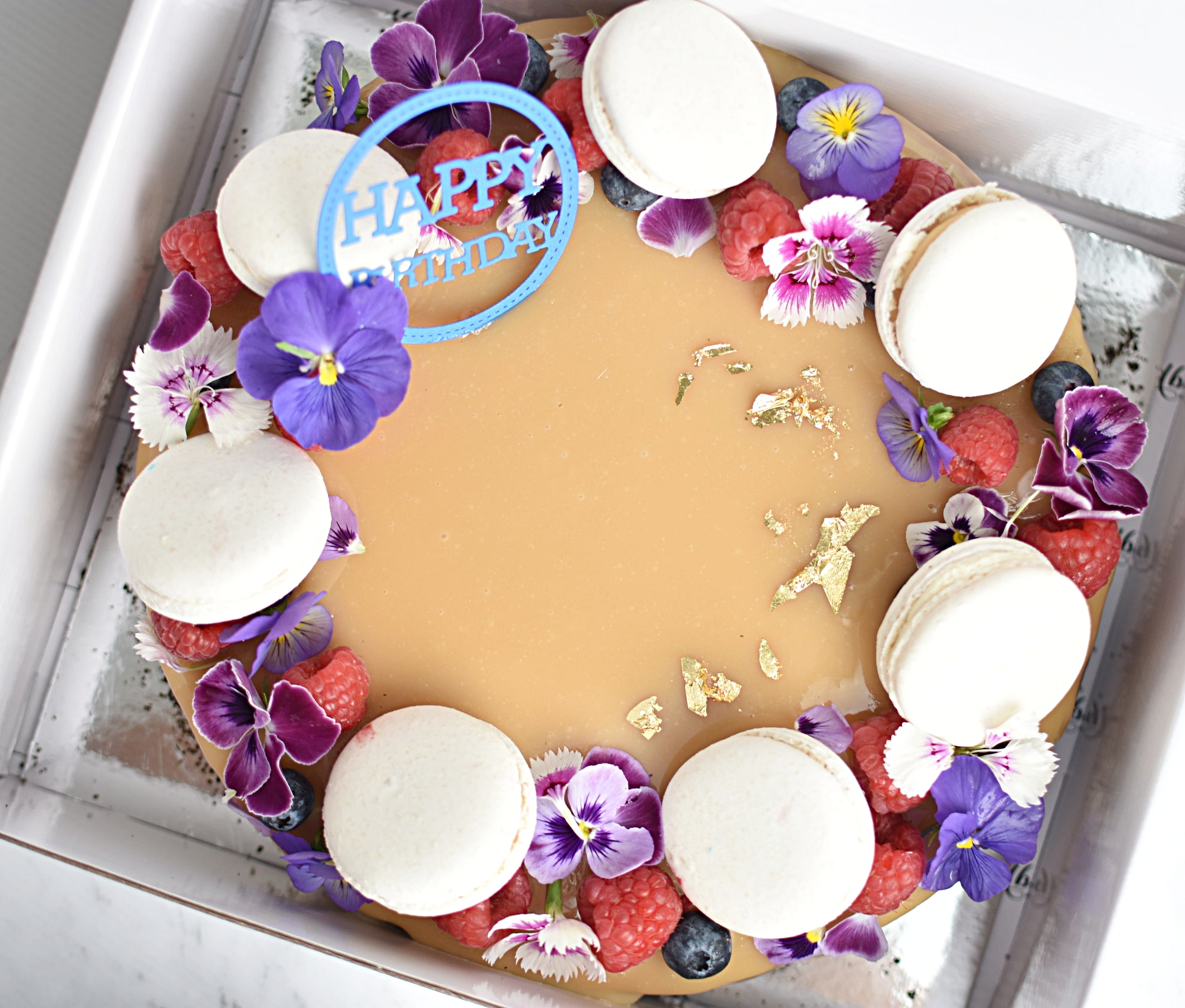 BANOFFEE ENTREMET  Banana Sponge Cake, Caramel Mousse, Milk Chocolate Mousse, Caramel Mirror Glaze, Chocolate and Caramel Macarons, Fresh Berries and Edible Flowers + Gold Leaf.  6' size $49.00 Feed upto 8  8' size $69.00 Feed upto 12