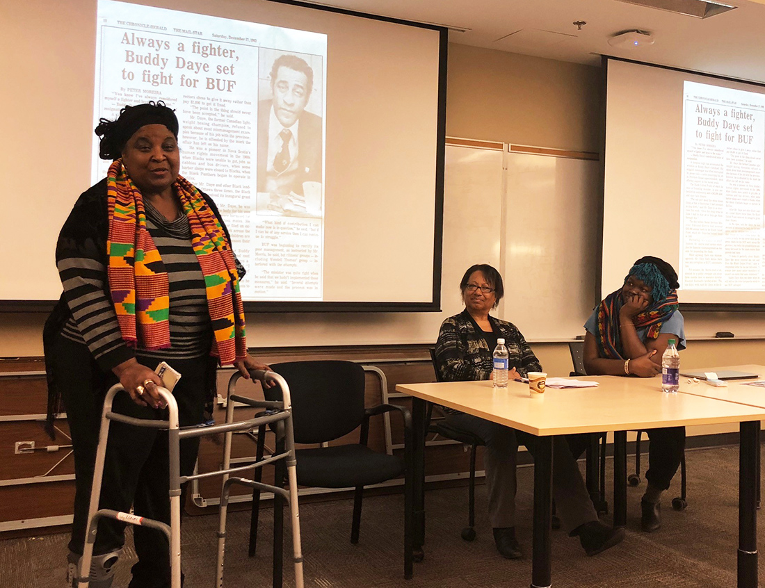 Dr. Lynn Jones addresses the audience as images from the Lynn Jones African-Canadian & Diaspora Heritage Collection appear in the slideshow behind her. The other panellists were Regina James (centre) of the East Preston Empowerment Academy, and researcher/filmmaker Francesca Ekwuyasi (at right).
