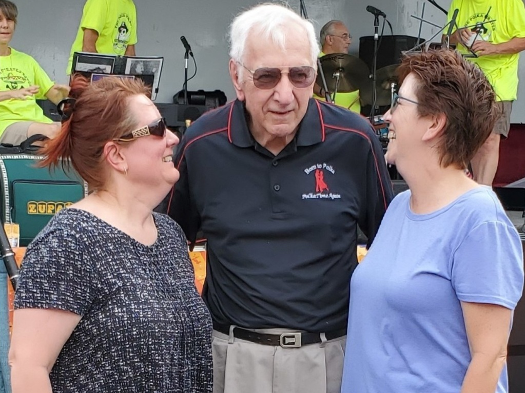 Gene Kovack presents Deb Arends and Lori Mae Reynolds with the third place prize in the 2019 polka dancing contest.
