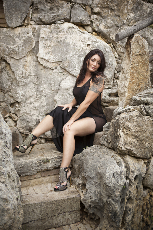 outdoor boudoir black dress on rocks in nature outdoors