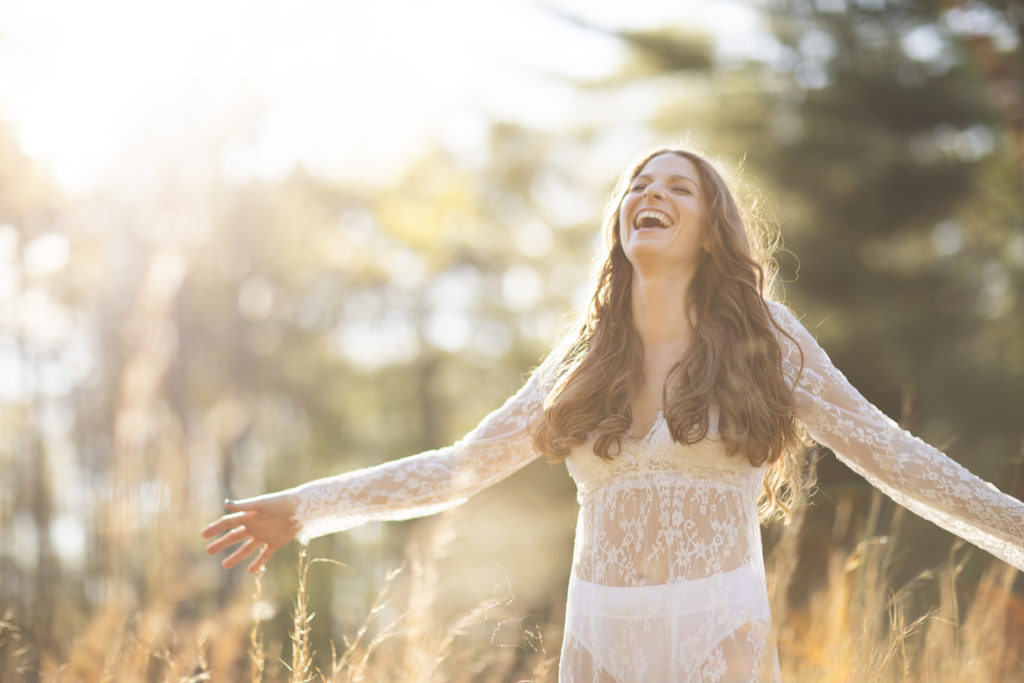 woman laughing golden sun white lace gown boudoir photography outdoors