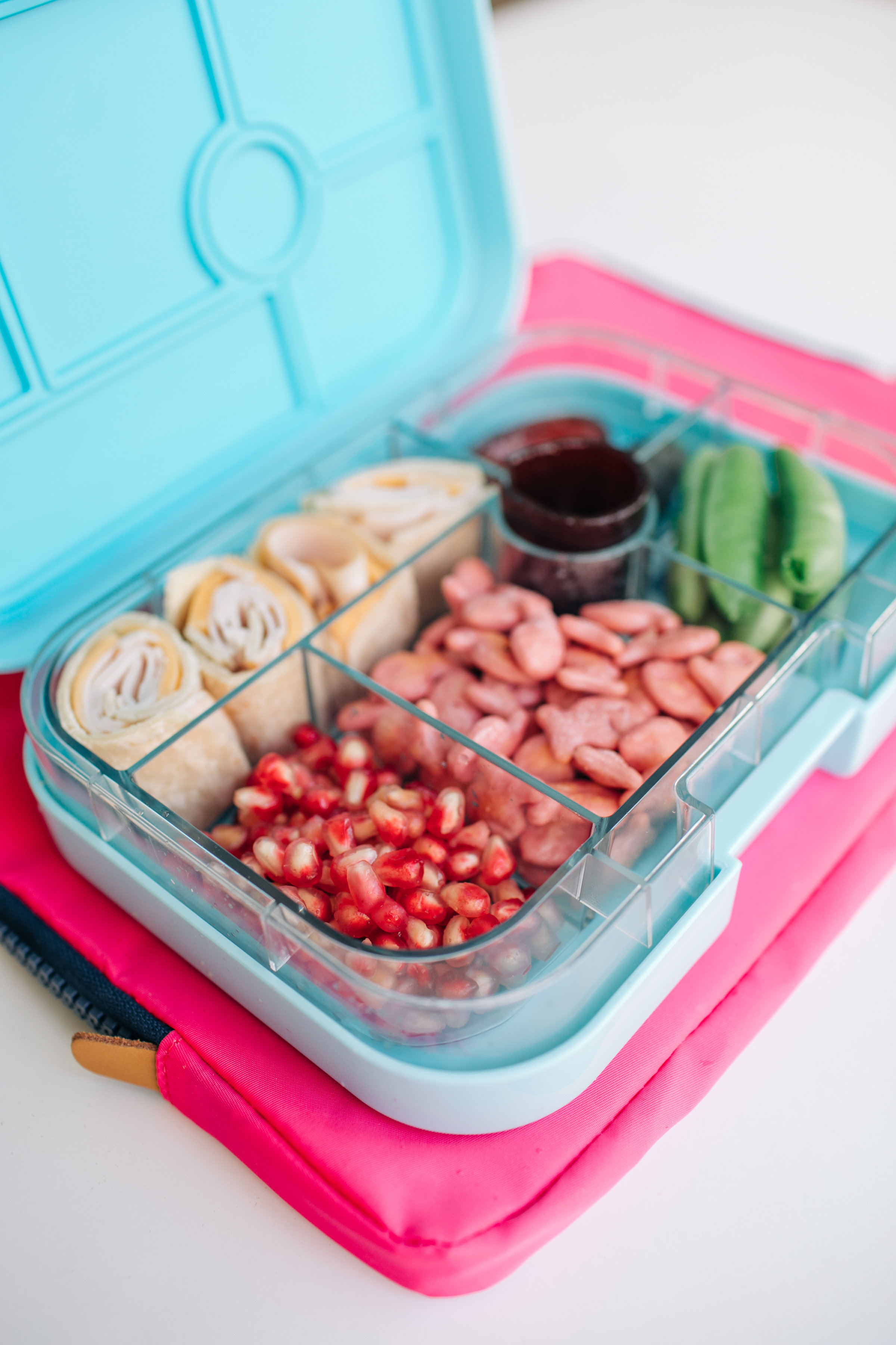 Turkey and Cheddar Tortilla Roll, Sugar Snap Peas, Fruit Leather, Goldfish Crackers, Pomegranate Seeds and two pitted Dates! This Yumbox here is the  Original  size.