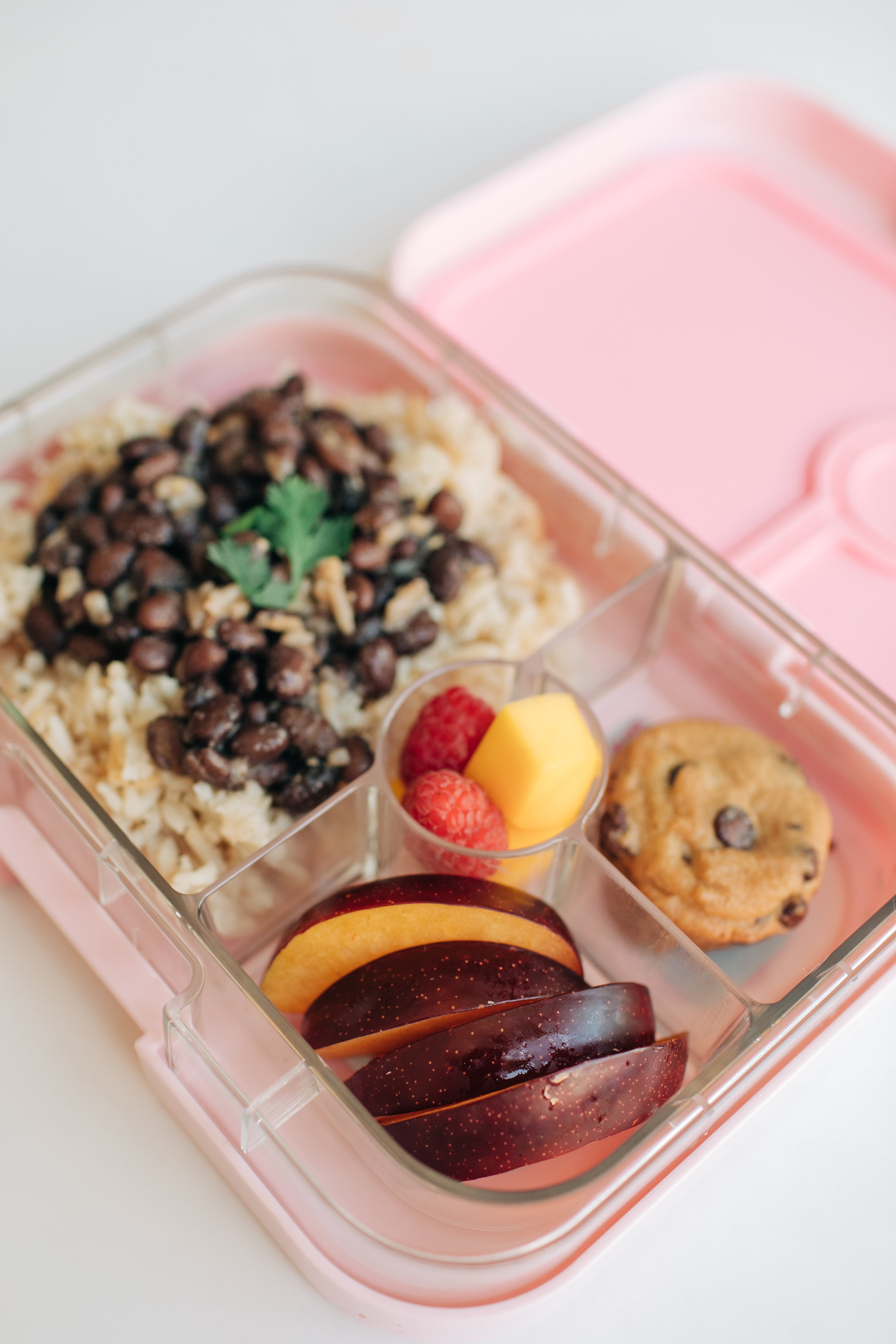 """This lunch is a favorite! Mila will eat rice for every meal if I'd let her. If you ask her what she wants for dinner she'll more than likely say """"Rice and beans!"""" or """"PIZZA!"""" She loves when I pack rice and beans for her lunch (her preschool warms it for her).  In this lunch here I've loaded up on fruit with raspberries, mango pieces, and plum slices. Two mini chocolate chip cookies and a portion of brown rice with black beans.  This Yumbox here is the  Panino  style!"""