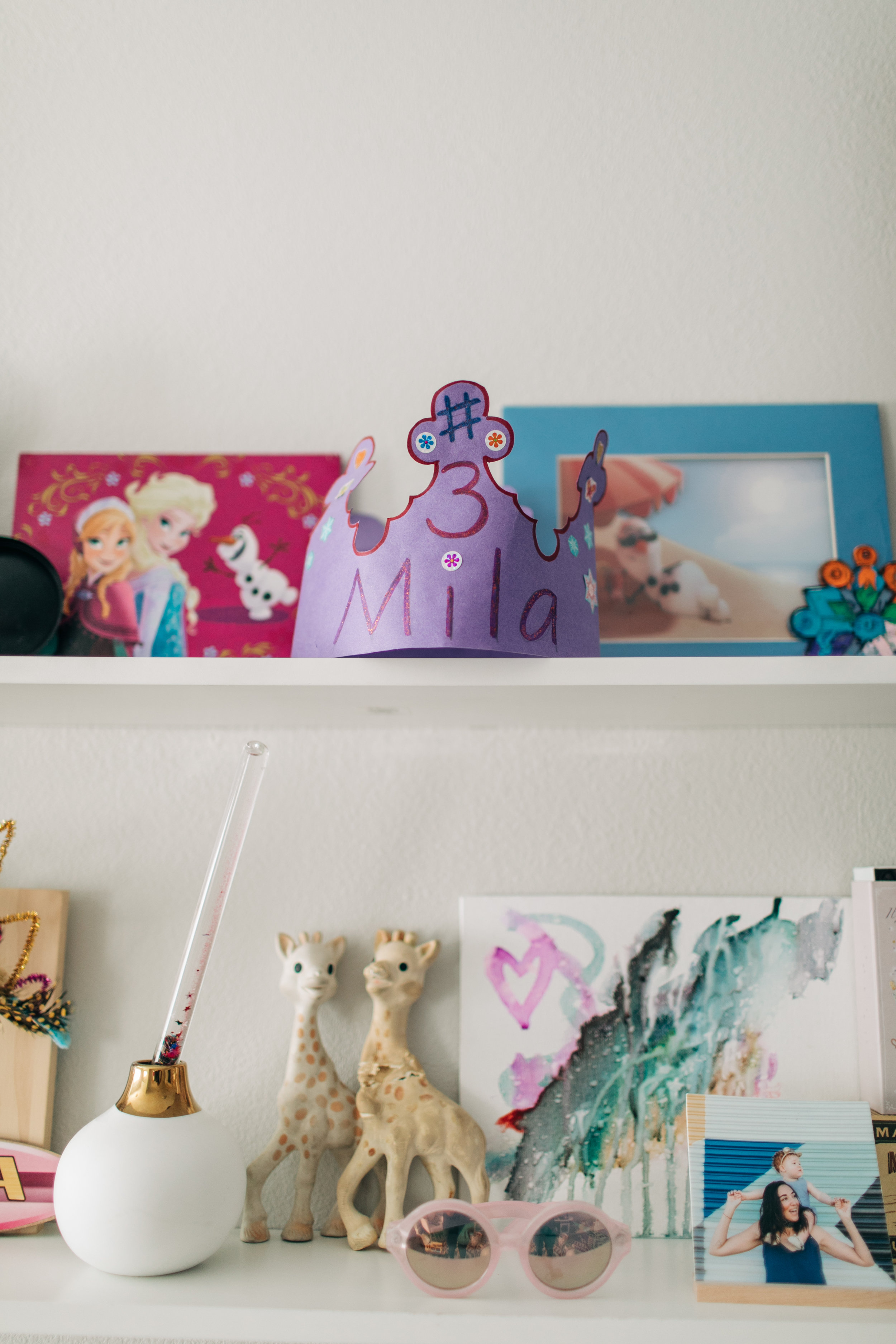 At the top there is a birthday crown Mila's teacher made her when they celebrated her birthday at school. I bought that art print of Olaf laying in the sand a few months after I lost Ryan. I love it so much. Also I have Ryan and Mila's Sophie Giraffe teethers displayed. Ryan's is nine years old now, they are both such treasures.