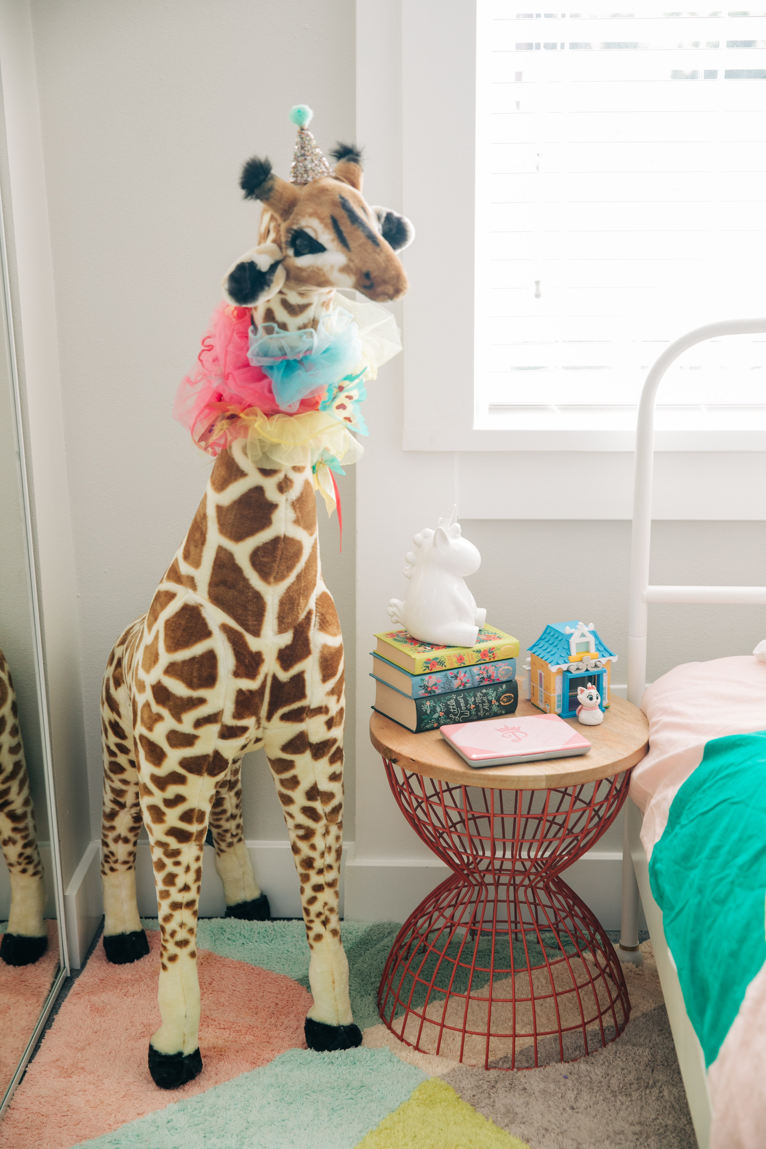 """This giant giraffe was a gift from my sister Jessica. Mila loves him and he is constantly getting dressed up. Right now he is looking fierce in a colorful boa and party hat!  On her bedside table rests some classic books we've had since we put together her nursery. A unicorn bank from Target and her """"laptop"""". Plus a little Disney cat toy Mila's Aunt bought for her. Mila loves keeping her special things in special places. That is one thing about her that I admire, she keeps her toys in specific places and they all have a home. (Unless they are being played with, then they are any and everywhere)"""