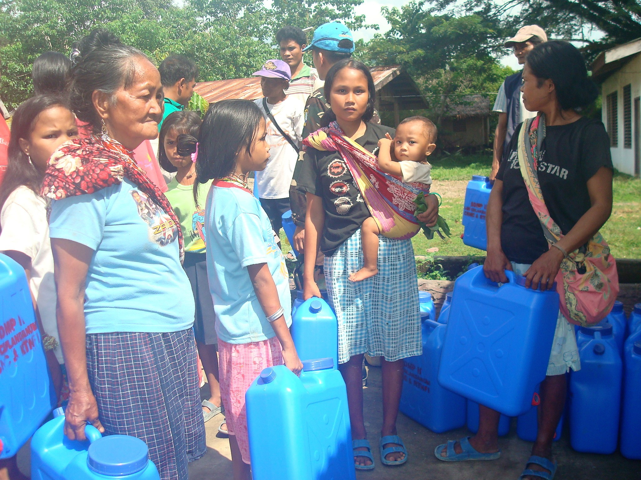 Local people line up with five-gallon water jugs to receive purified water at a water distribution area in Culandanum, Palaw-an. Photo by  US Marine Corps, Pacific .