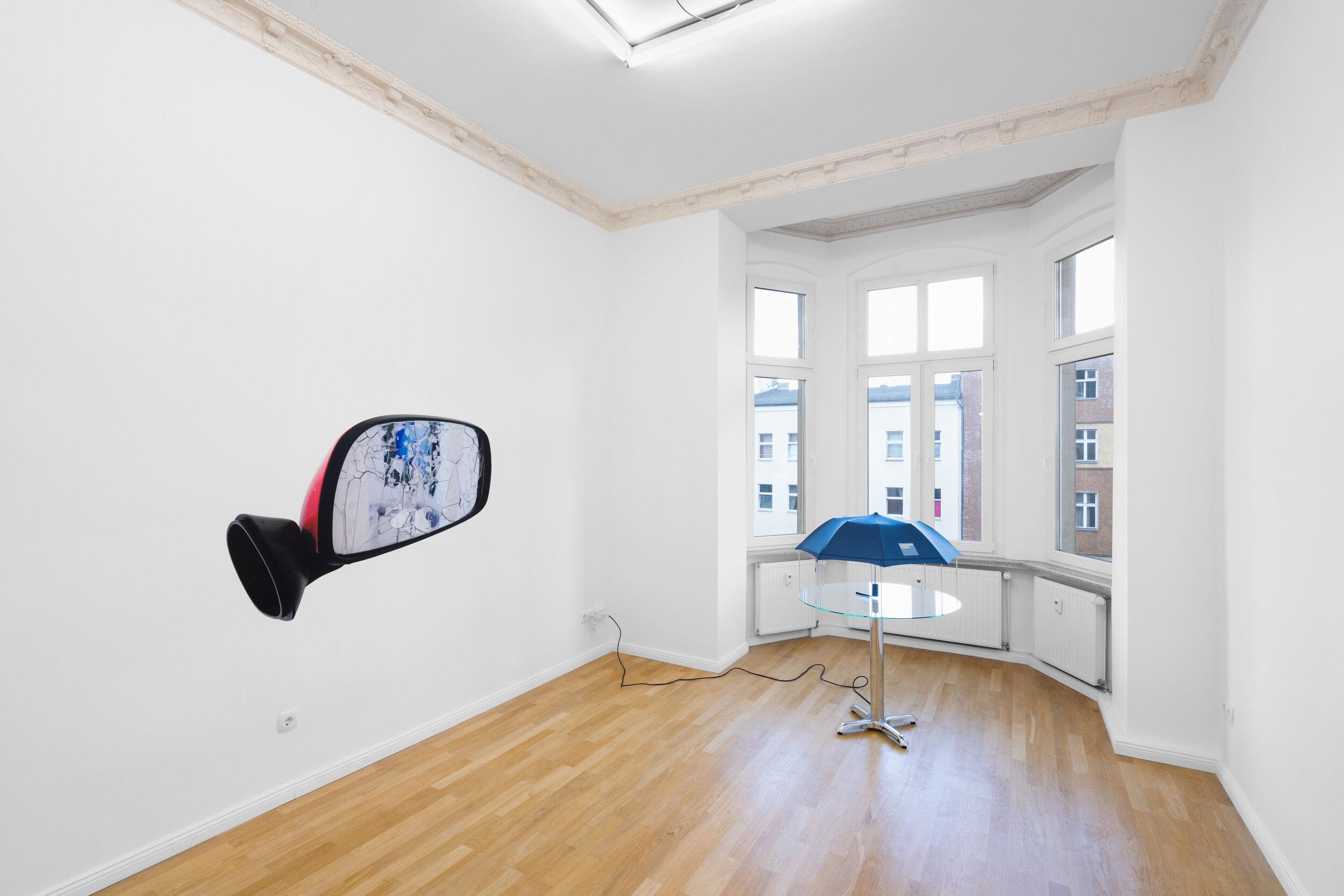 Installation view,  Andrew J. Greene, Madeline Hollander, Asha Schechter  Left: Asha Schechter,  Prius mirror from Baby Barcelona , 2019 Right: Andrew J. Greene,  Umbrella Dryer (Goldman Sachs) , 2017/2019