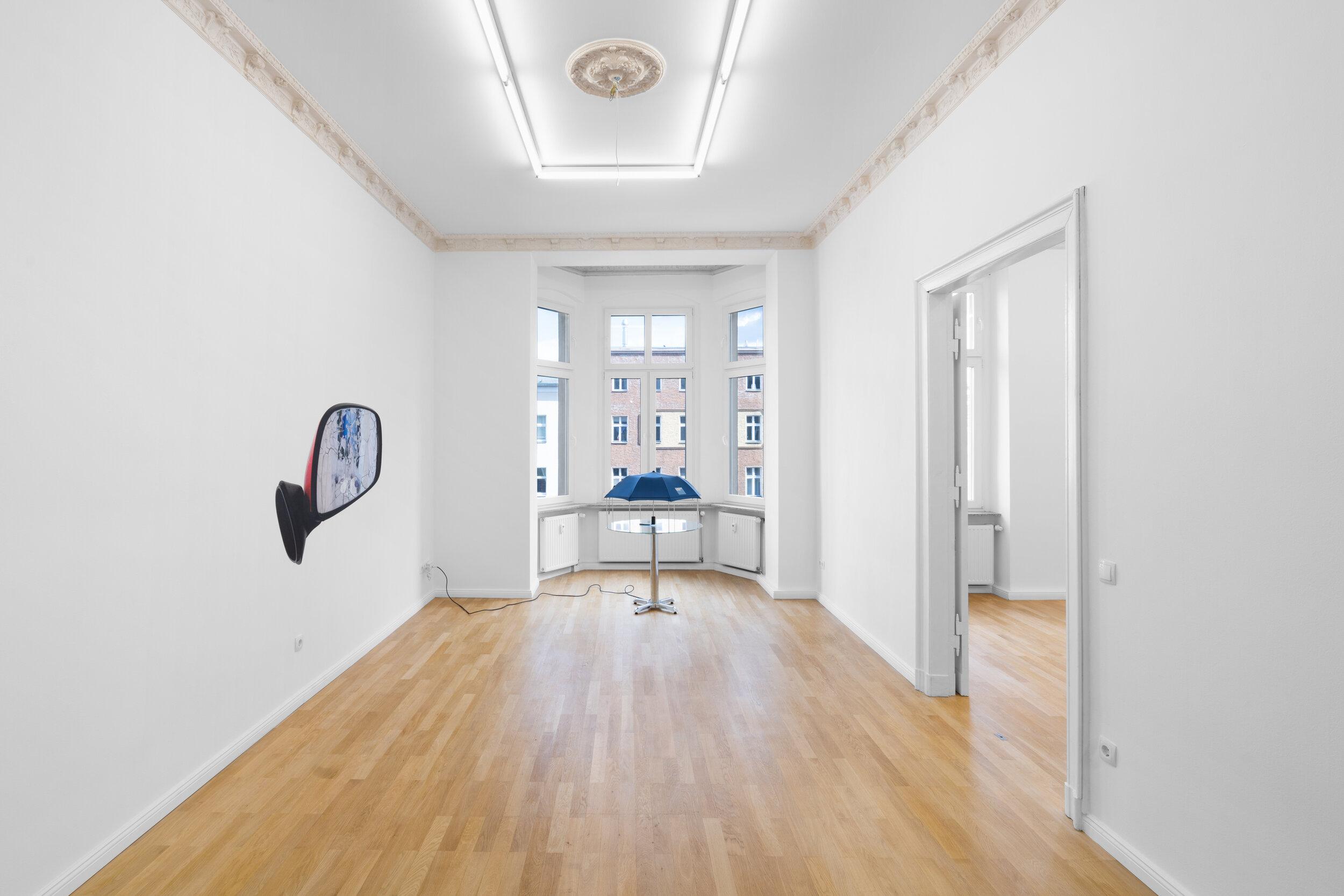 Installation view,  Andrew J. Greene, Madeline Hollander, Asha Schechter  Left: Asha Schechter,  Prius mirror from Baby Barcelona , 2019 Center: Andrew J. Greene,  Umbrella Dryer (Goldman Sachs) , 2017/2019