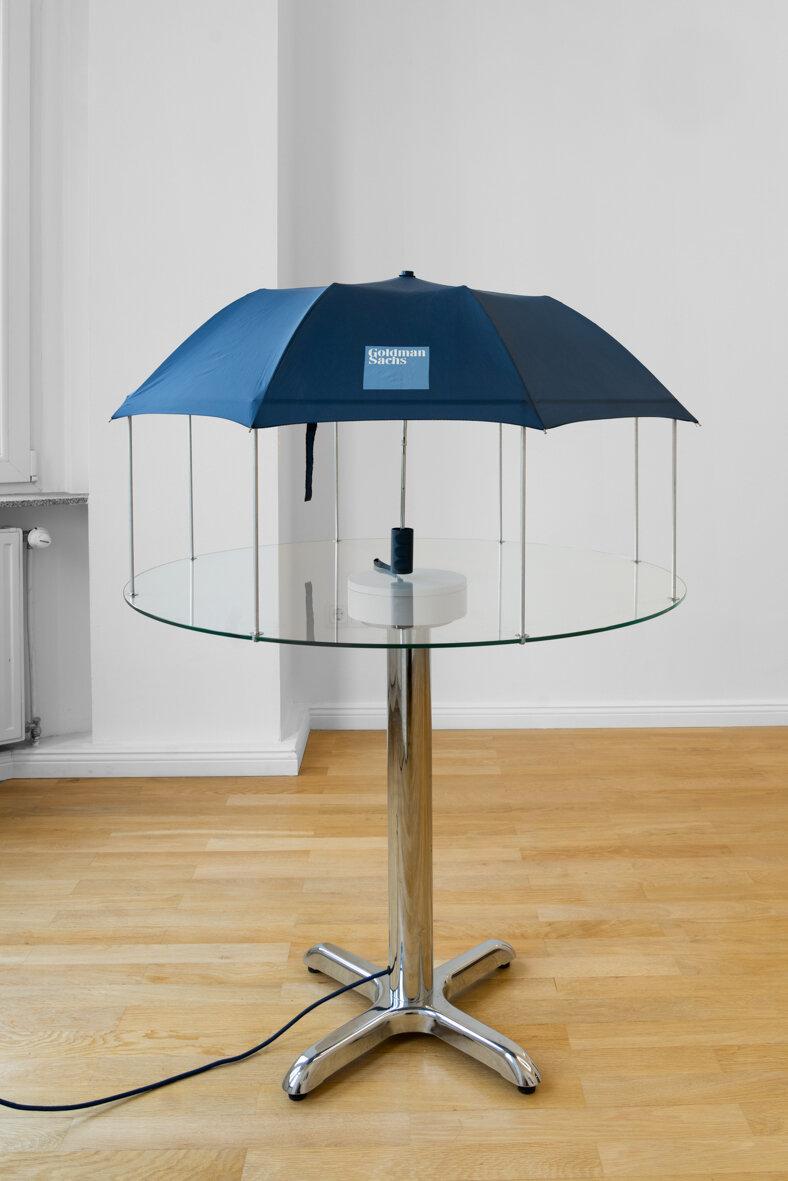 Andrew J. Greene,  Umbrella Dryer (Goldman Sachs) , 2017/2019 Umbrella, aluminum tubing, glass, motorized turntable, chrome table base 127 x 91.5 x 91.5 centimeters, 50 x 36 x 36 inches   Additional video documentation here.