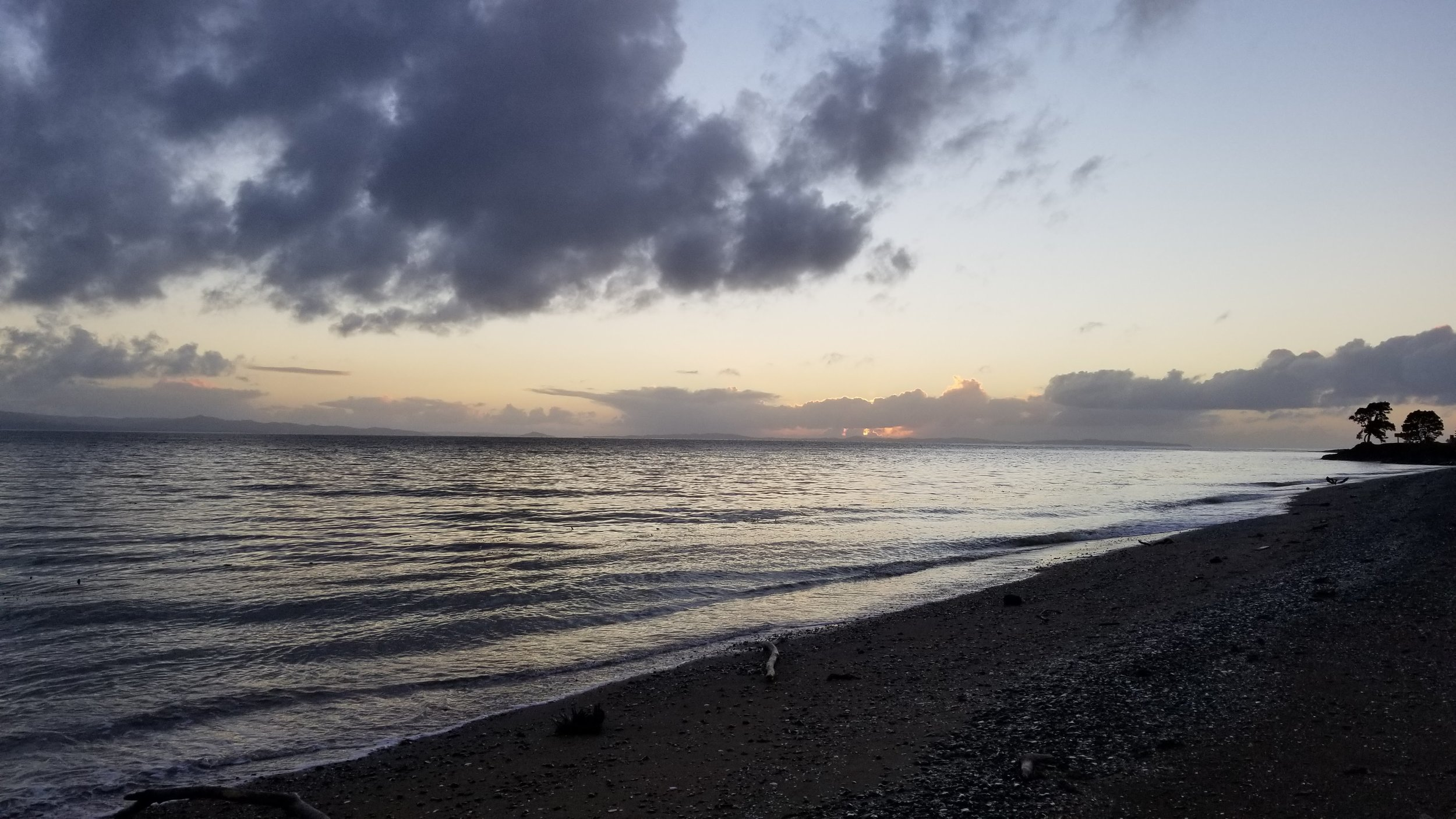sun hidden by clouds from the shore of the Coromandel Peninsula, across the Firth of Thames