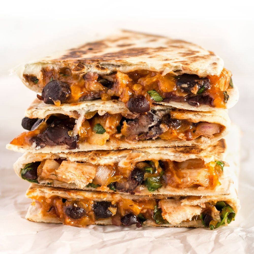 ULTIMATE BBQ CHICKEN QUESADILLAS - 1.5 cups chopped cooked chicken15 oz can black beans, drained1/4 red onion1 jalapeño1/2 cup fresh cilantro2 cups shredded cheddar1 tsp chili powder1/2 tsp smoked paprika1/4 tsp salt1/2 cup Sweet Baby Ray's BBQ Sauce10 7 inch flour tortillasSee it here
