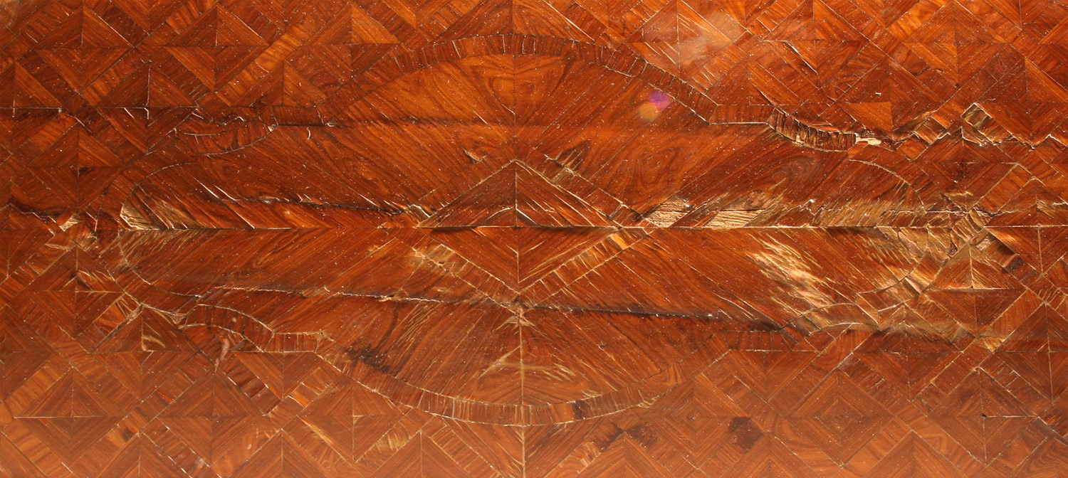 Decorative veneered surface with damage caused by wear, water, and substrate movements