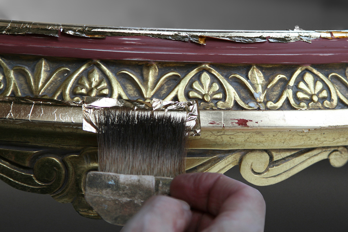 Gold leaf is gently applied to areas of gilding loss