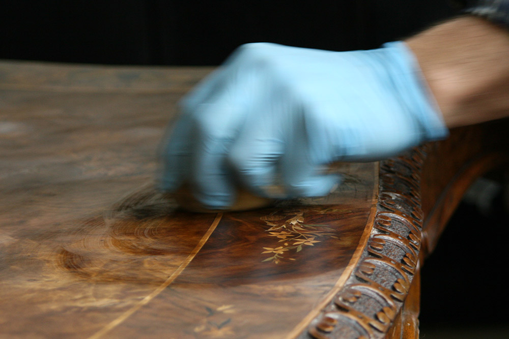 The first layer of French polish is applied to the restored table surface. Soon, shellac will immediately highlight marquetry patterns and wood grain
