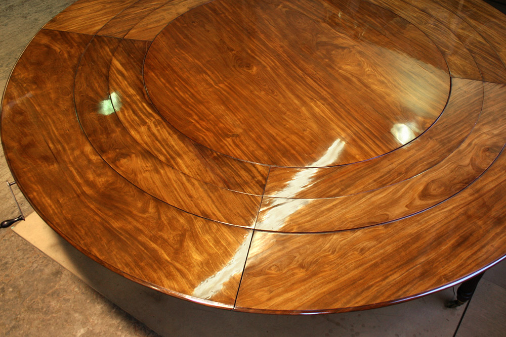 Detail of restored table top with all the extension leaves aligned in place
