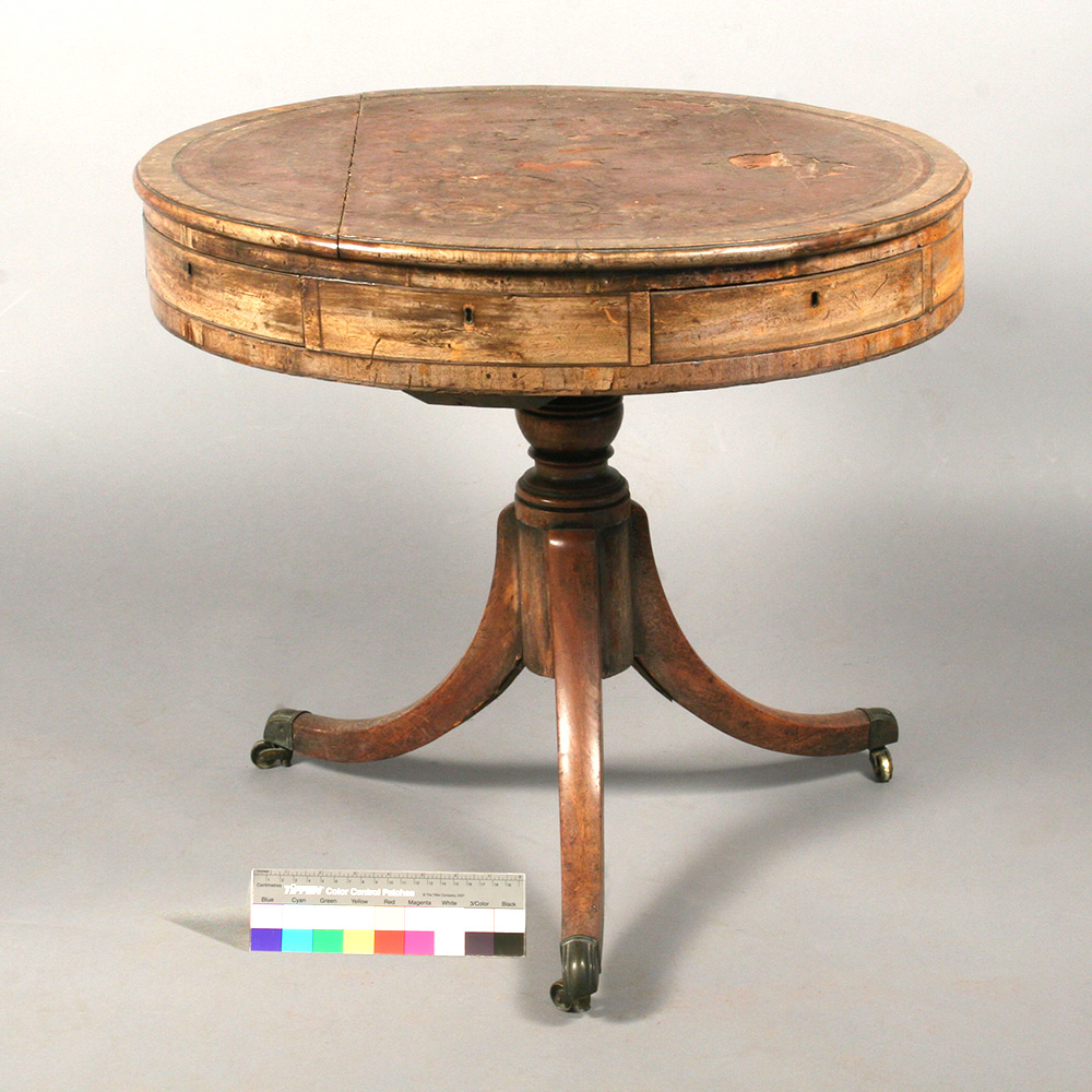 Drum table with with visible damage related to structure, leather top, and finish