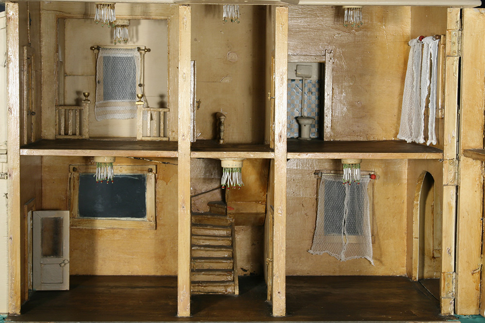 Photo:  The historic dollhouse interior features original and working light fixtures, rail decorative moldings, authentic curtains and curtain rods, conserved bathroom wallpaper and appliances, and preserved wood floors throughout the entire house. All the doors have working hinges and knobs. The glass panels are all in place.