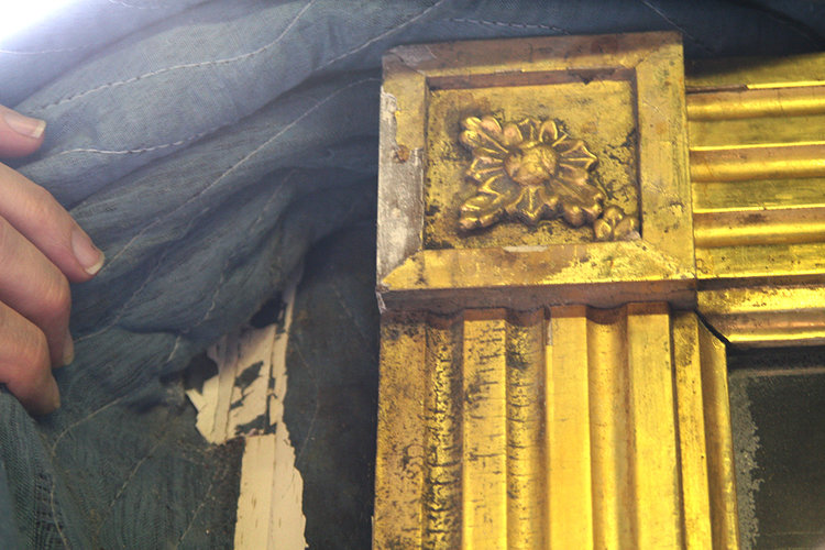 Damage that happened to the giltwood mirror when moisture exposure caused the moving pad to become attached to the water based gilding. The pad could not be removed without damaging the gilt surface.