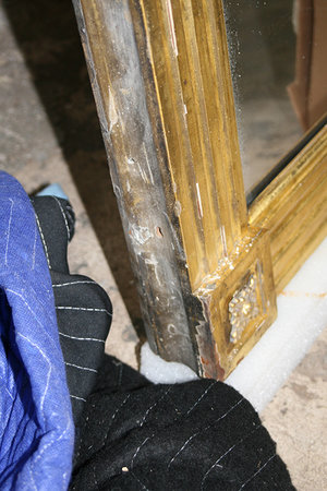 Damaged corner of the gilded frame affected by moisture exposure which caused excessive mold growth, missing and loose gesso layer, and cracked wooden substrate