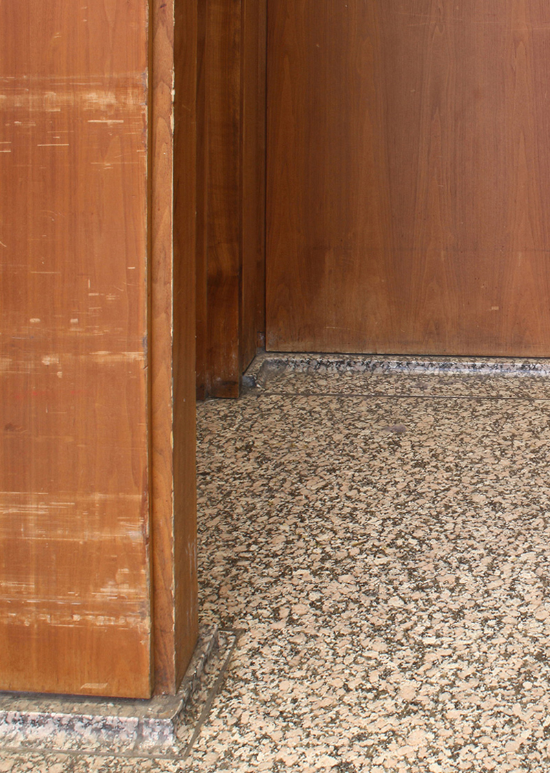Detail of veneered panels and trims at floor level with visible damage from contact with Post Office carts and cleaning equipment | Photo courtesy of GSA