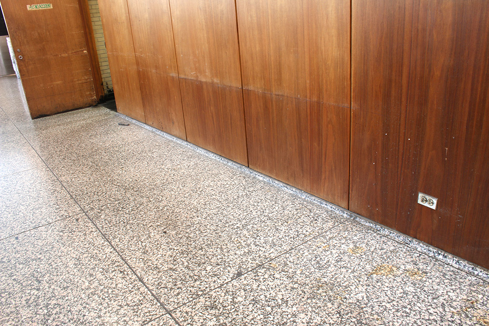 This wide angle photograph captures the extent of deterioration of the veneered panels and the adjacent door caused by contact with metal Post Office carts over many years. | Photo courtesy of GSA