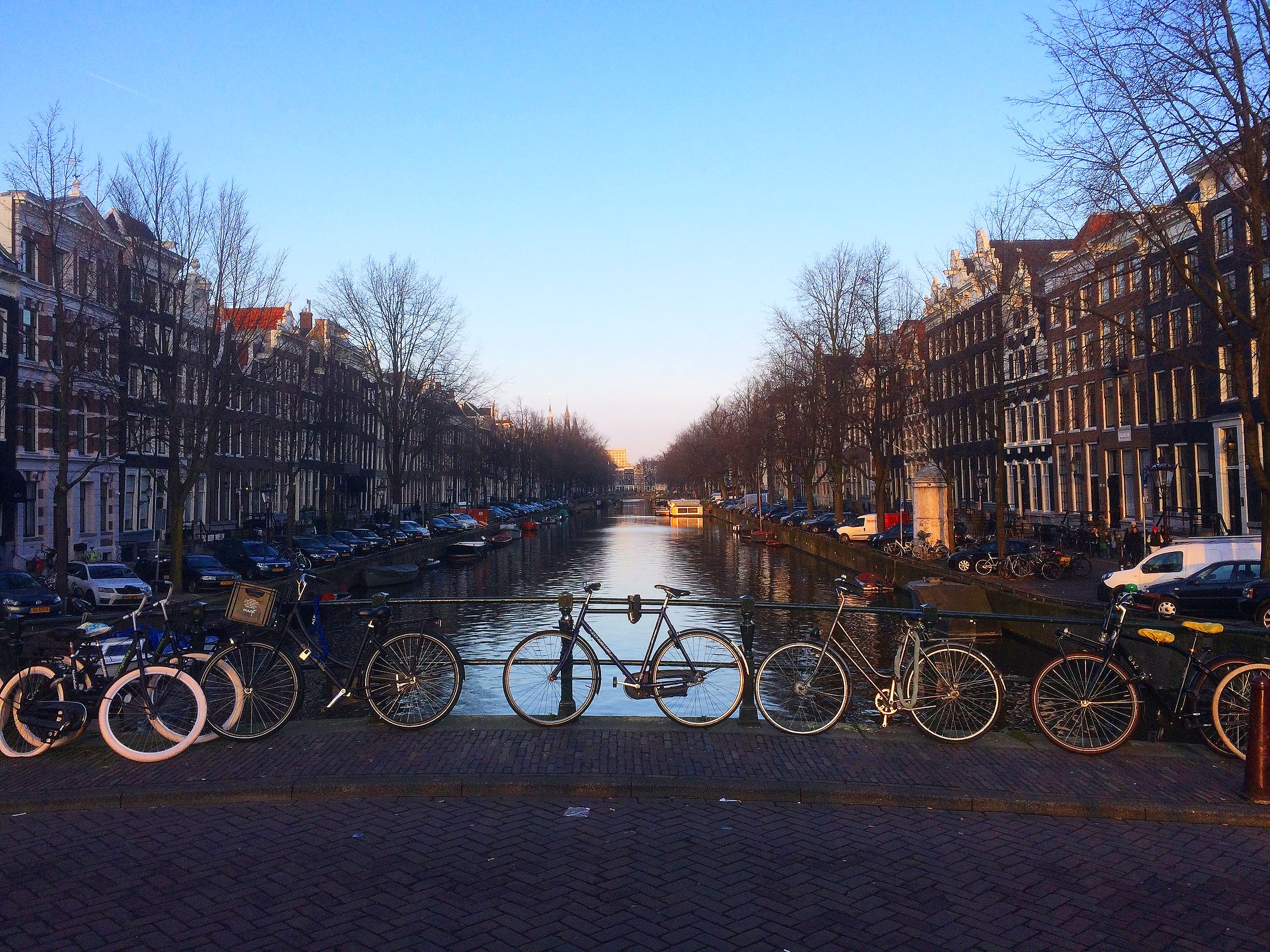 bikes chained to a bridge railing in Amsterdam
