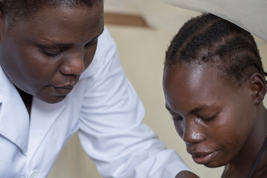 A midwife and mother look down at a baby in Uganda