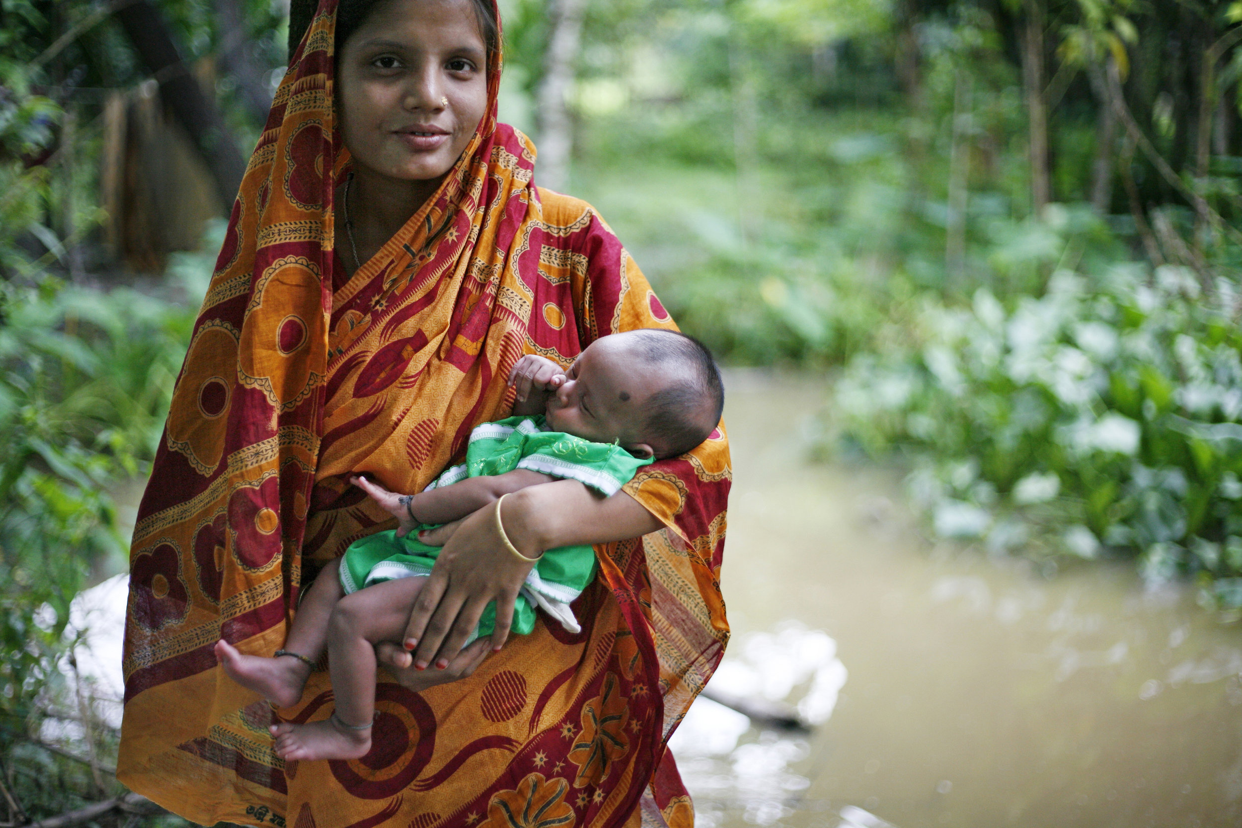 A young mother holds her baby in Bangladesh