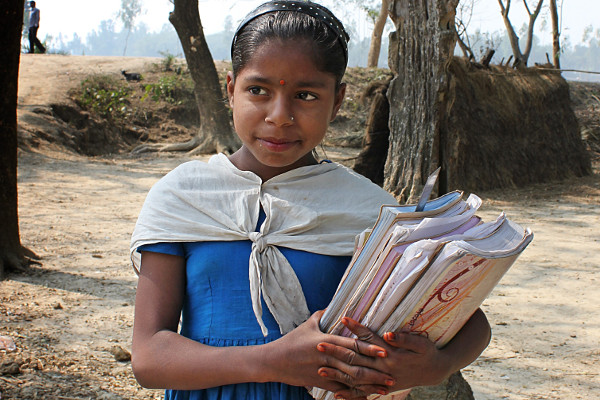 A young girl holds books to help her with studying
