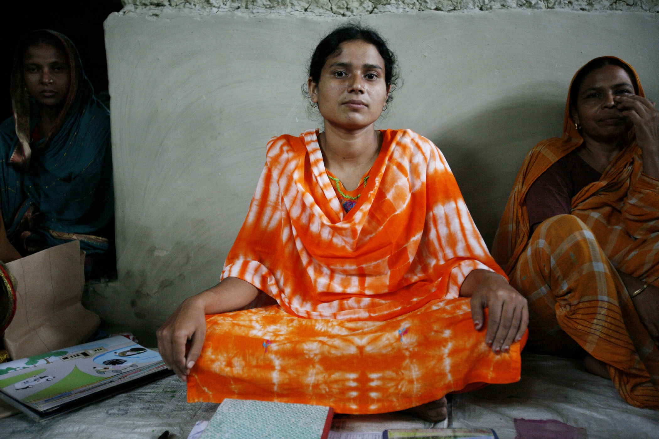 A woman places her hands on her lap in their community health meeting