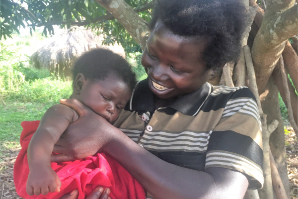 Janet and her baby pose playfully outside of their group meeting in Uganda