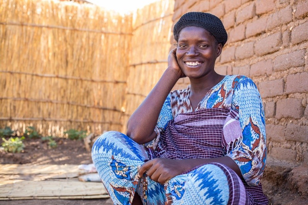 Pregnant mother, Adesi, sitting near her community health group in Malawi