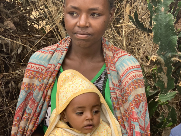 Birkinesh holds her baby whilst recounting the difficulties she had in labour. By building a road, it takes now just 15 minutes to get to hospital