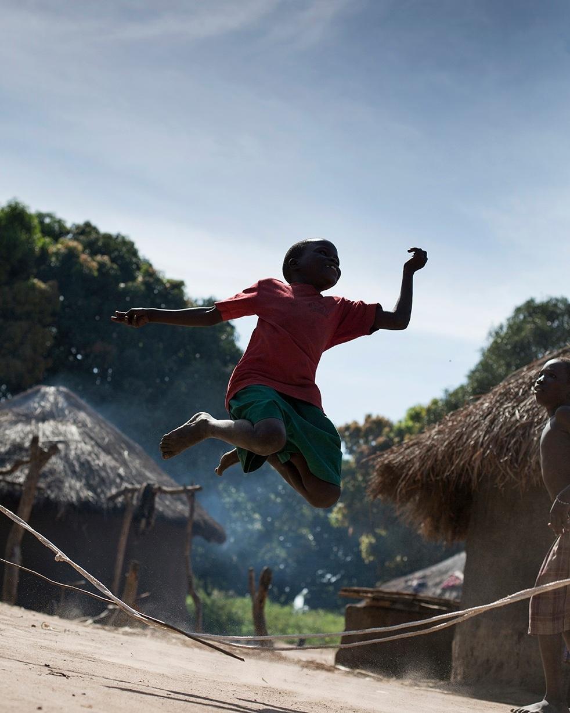 A child skips in Padun Latwong Village, Uganda