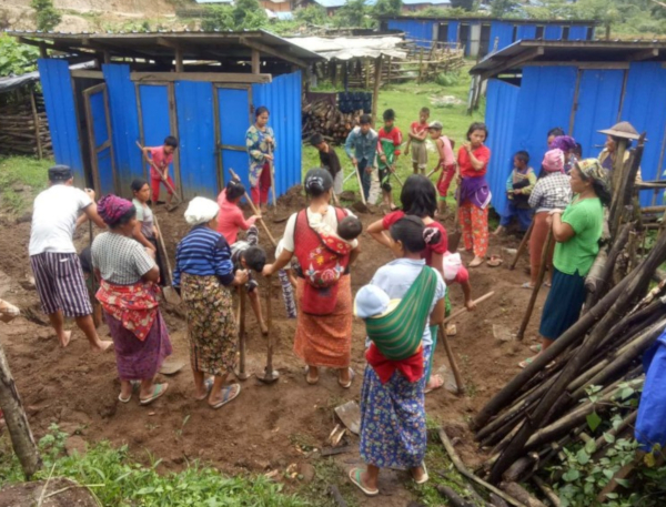 The Community Health Group and other villagers build the sheltered latrines together
