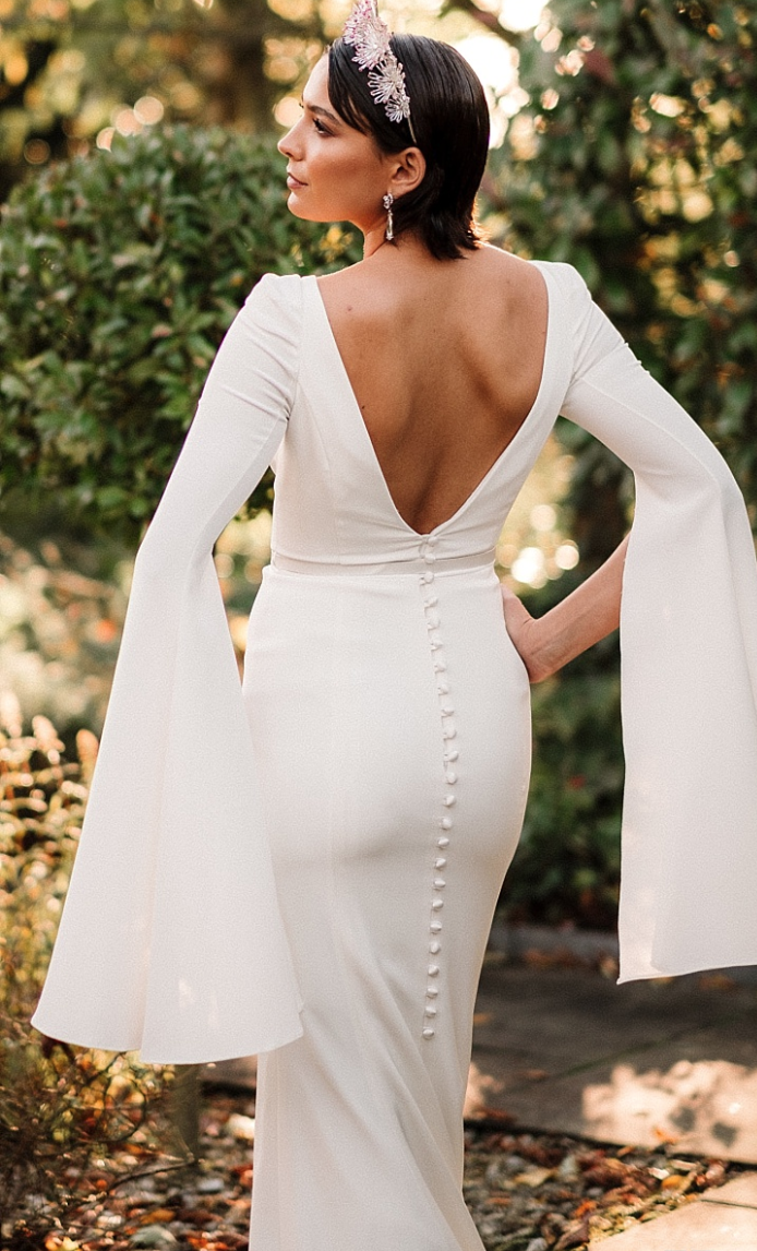 / 6 - SASSI HOLFORD | HARRIETStylish Harriet is a chic column gown with split 70's bell sleeves and shoulder pads – style with a slim satin belt or gold embelishment