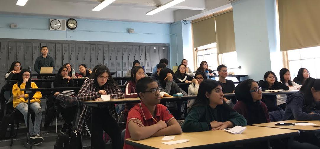 AP Capstone students evaluate a classmate's presentation on financial instability in the modern era.    Photo Credit: Haseeb Khan