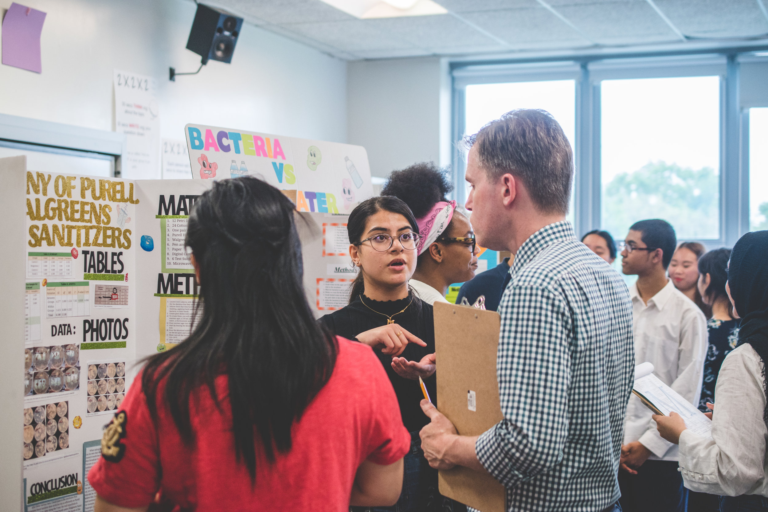 Maham Ghori '21 explains the results of her research on hand sanitizers to Dr. Trevor Stokes, a biology teacher and judge for the science fair.  Photo Credit: Justin Chow
