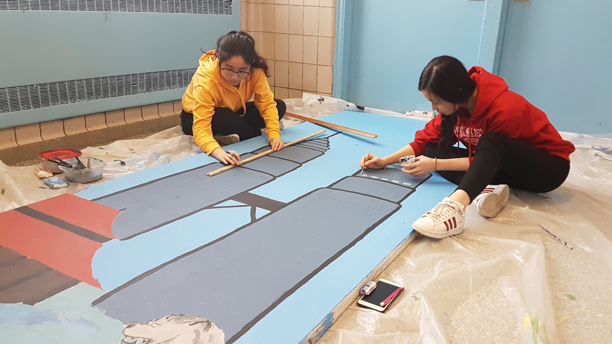 The Art Crew works on backgrounds for the stage.  Photo Credit: Shamail Naseer