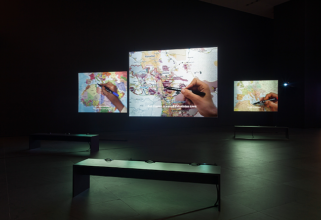 Bouchra Khalili. The Mapping Journey Project. 2008-2011. Eight-channel video (color, sound). Installation view, Bouchra Khalili: The Mapping Journey Project, The Museum of Modern Art, New York, April 9 – August 28, 2016. The Museum of Modern Art, New York. Fund for the Twenty First Century, 2014. © 2016 Bouchra Khalili. Digital image © 2016 The Museum of Modern Art. Photo: Jonathan Muzikar.