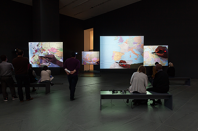 TOP AND BOTTOM: Bouchra Khalili, 'The Mapping Journey Project' 2008-2011. Eight-channel video (color, sound). Installation view at The Museum of Modern Art, New York, April 9 – August 28, 2016. The Museum of Modern Art, New York. Fund for the Twenty First Century, 2014. © 2016 Bouchra Khalili. Digital image © 2016 The Museum of Modern Art. Photo: Jonathan Muzikar